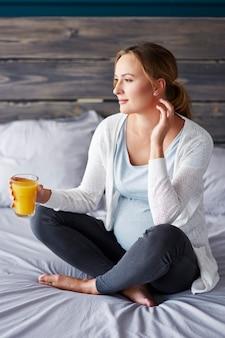 Zwangere vrouw met sinaasappelsap in slaapkamer