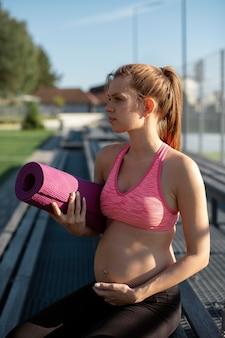 Zwangere vrouw met sportuitrusting