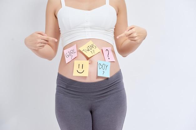 Zwangere vrouw met stoknota's over haar buik