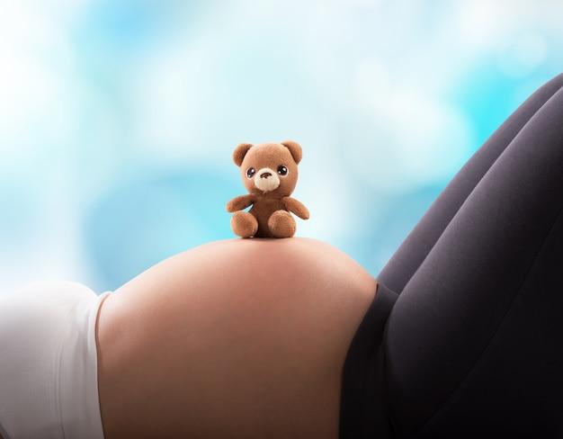 Zwangere vrouw met teddybeer op buik