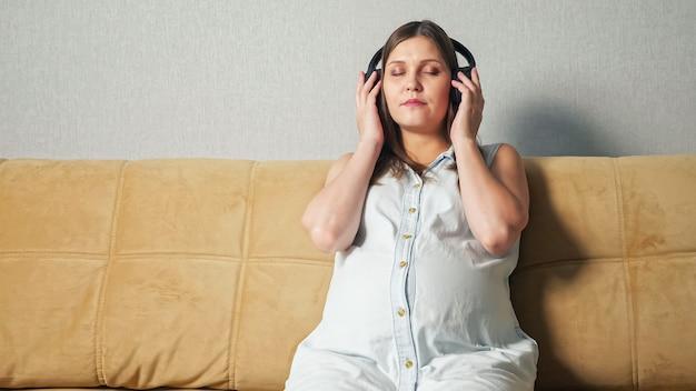 Zwangere vrouw met telefoon die koptelefoon op zet terwijl ze op de bank zit