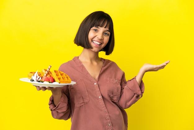 Zwangere vrouw met wafels geïsoleerd op een gele achtergrond die de handen naar de zijkant uitstrekt om uit te nodigen om te komen