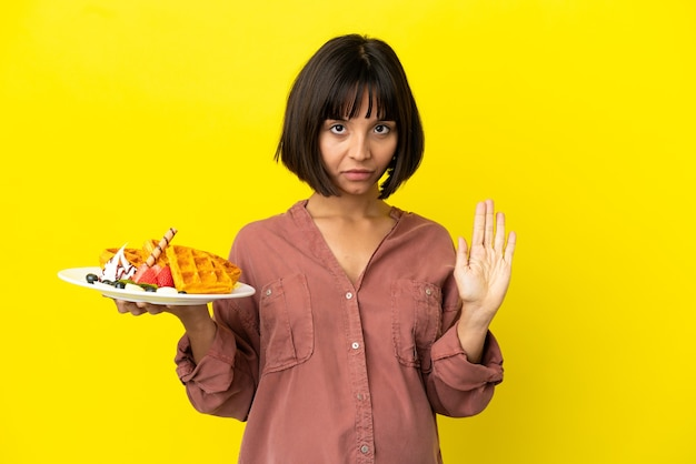 Zwangere vrouw met wafels geïsoleerd op een gele achtergrond die stopgebaar maakt