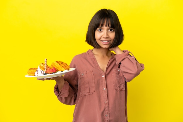 Zwangere vrouw met wafels geïsoleerd op gele achtergrond die een idee denkt terwijl ze omhoog kijkt