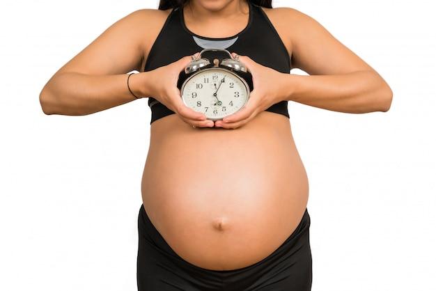 Zwangere vrouw met wekker.
