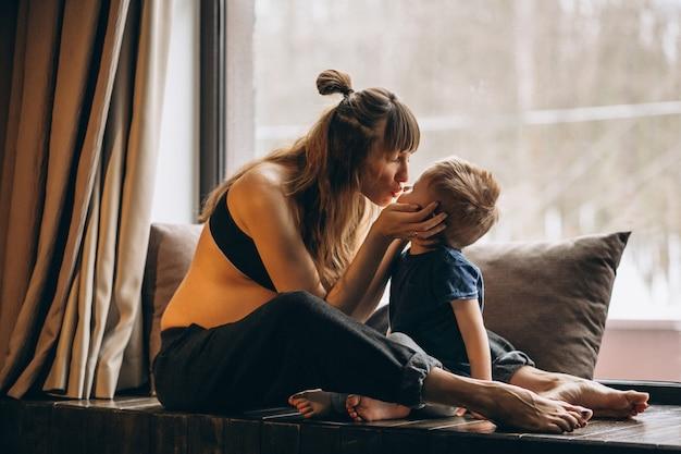 Zwangere vrouw met zoon zit bij het raam