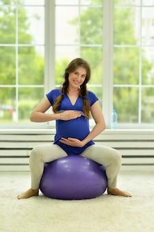 Zwangere vrouw oefeningen met gymnastiekbal thuis