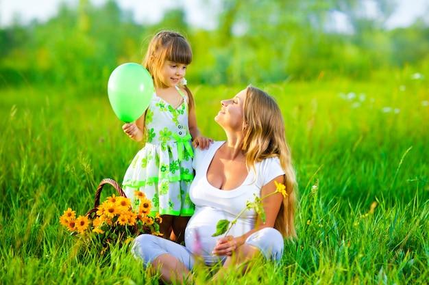 Zwangere vrouw op veld en meisje met ballon