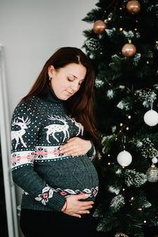 Zwangere vrouw poseren in de buurt van de kerstboom thuis merry christmas