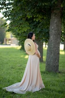 Zwangere vrouw poseren in een beige jurk op een achtergrond van groene bomen.