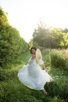 Zwangere vrouw poseren in een witte jurk op een achtergrond van de natuur.