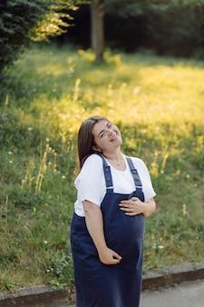 Zwangere vrouw poseren in het park
