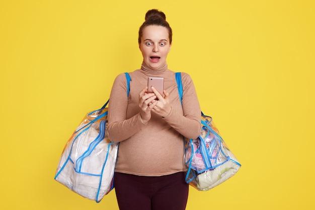 Zwangere vrouw praten over haar slimme telefoon en bellen, ambulance, voelt weeën, slimme telefoonscherm kijken met geschokte gezichtsuitdrukking, toekomstige moeder gaat naar het ziekenhuis liggen.