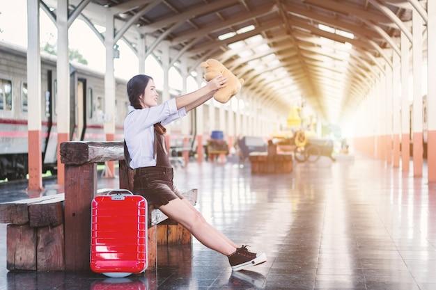 Zwangere vrouw reiziger zittend op knuffelen teddy beer met een rode koffer op spoorweg stati
