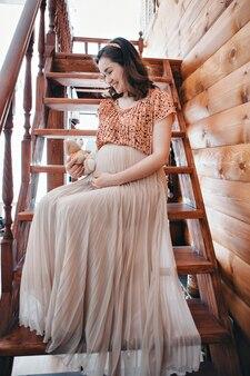 Zwangere vrouw spelen met teddybeer.