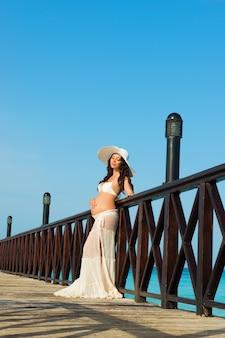 Zwangere vrouw staat op een houten pier op de achtergrond van de zee. dominicaanse republiek, de caribische zee.