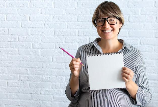 Zwangere vrouw teken voor de tekst, met lege witte kaart in de buurt van buik
