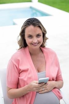 Zwangere vrouw texting bij het zwembad