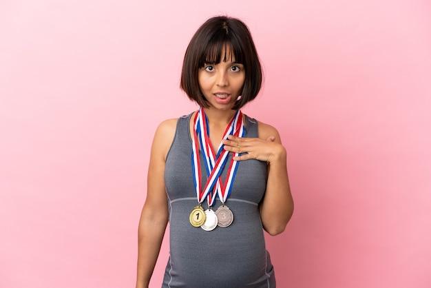 Zwangere vrouw van gemengd ras met medailles geïsoleerd op roze achtergrond verrast en geschokt terwijl ze naar rechts kijkt