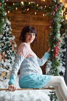 Zwangere vrouw wacht op kerstmis in de buurt van de kerstboom. zwangerschap en wachten op de geboorte van een kind. moederschap. rusland, sverdlovsk, 31 december 2018