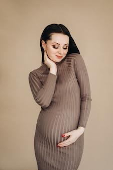 Zwangere vrouw wat betreft buik met haar handen