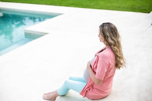 Zwangere vrouw wat betreft haar buikzitting naast de pool