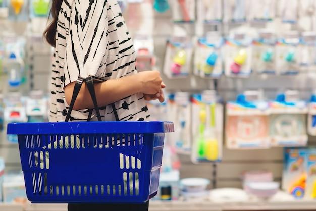 Zwangere vrouw winkelen in babywinkel. vrouw die babyspullen kiest in de winkel van de babywinkel. moeder kiest een pasgeboren babyproduct in de supermarkt. zwangerschap en winkelen.