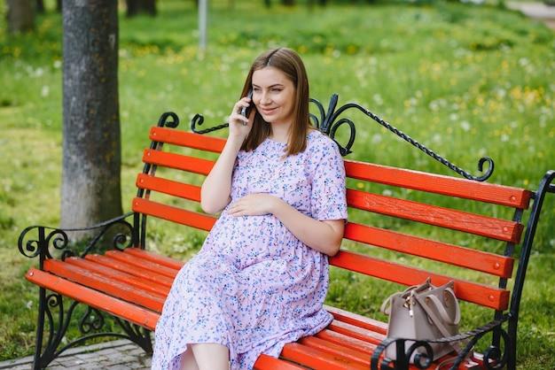 Zwangere vrouw zit op bankje in het park en met behulp van telefoon. gelukkige vrouwtjes hebben rust buiten tijdens de wandelingen