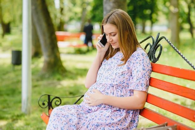 Zwangere vrouw zit op bankje in het park en met behulp van telefoon
