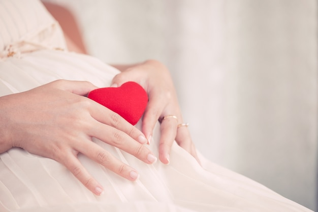 Zwangere vrouw zitten en het maken van hand hart vorm met rood hart op haar grote buik, moeder liefde baby