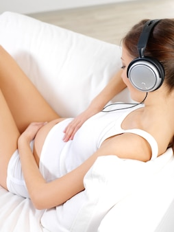 Zwangere vrouw zittend op een witte bank thuis en luisteren muziek in koptelefoon
