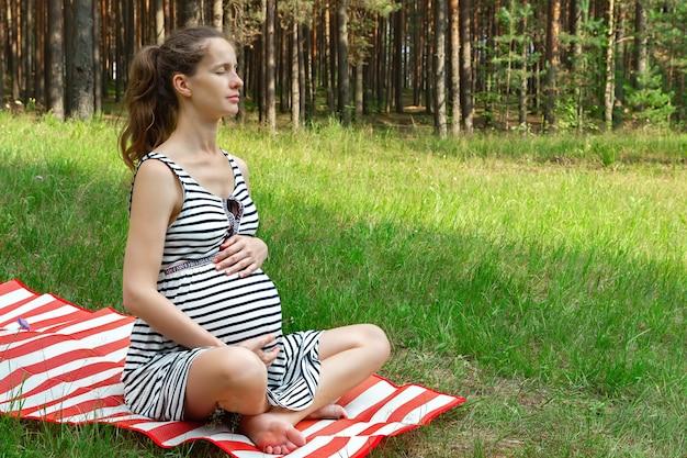 Zwangere vrouw zittend op het gazon met gras op de mat en buiten mediteren met gesloten ogen