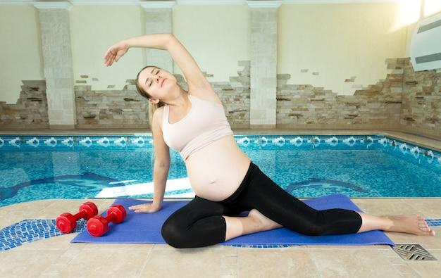 Zwangere vrouw zittend op mat naast zwembad en stretching