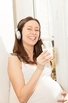 Zwangere vrouwen drinken een glas melk en luisteren naar muziek