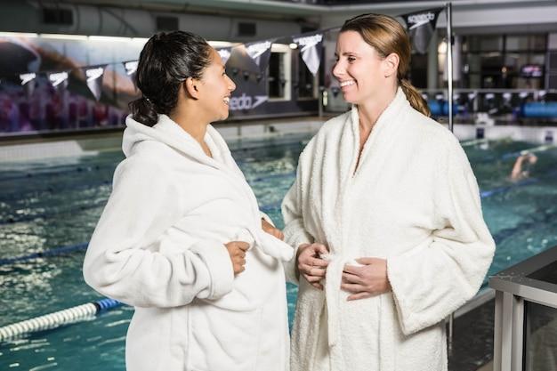 Zwangere vrouwen met badjas die bij het zwembad spreken