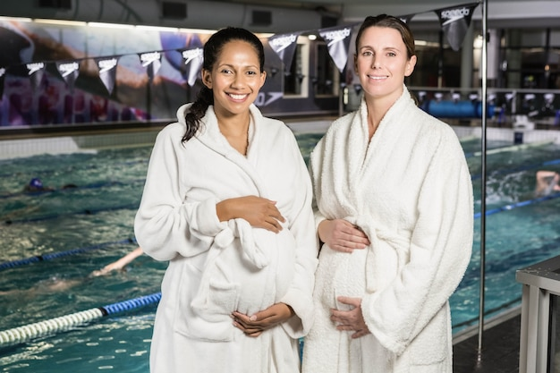 Zwangere vrouwen met badjas wat betreft hun buiken bij het zwembad