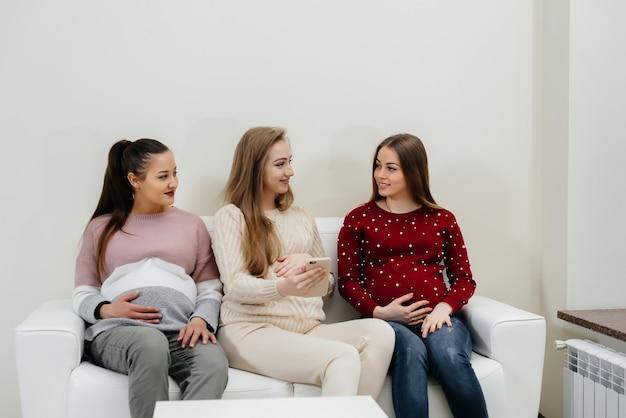 Zwangere vrouwen zitten op de bank en hebben plezier met elkaar te kletsen. zwangerschap en zorgen voor de toekomst van het kind