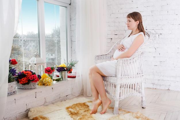 Zwangere vrouwen zitten op stoel het ontspannen dichtbij venster