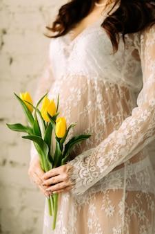 Zwangere vrouwenbuik met tulpenbloemen