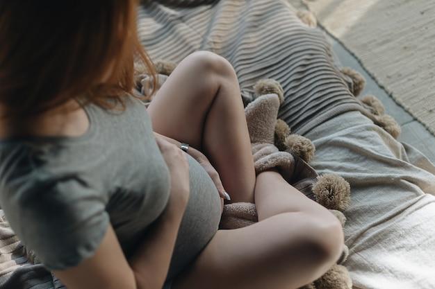 Zwangere vrouwenhanden die buik in verwachting omhelzen