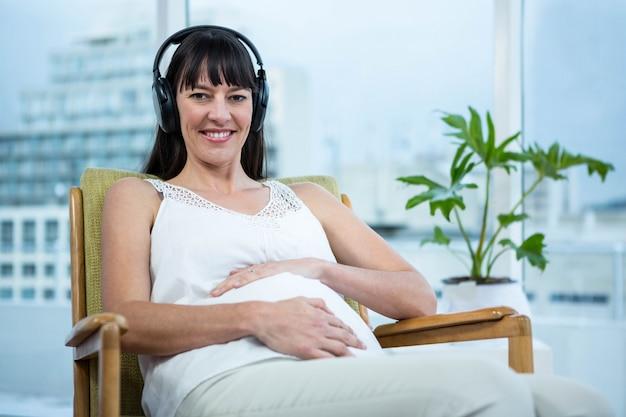 Zwangere vrouwenzitting op stoel en thuis het luisteren aan muziek