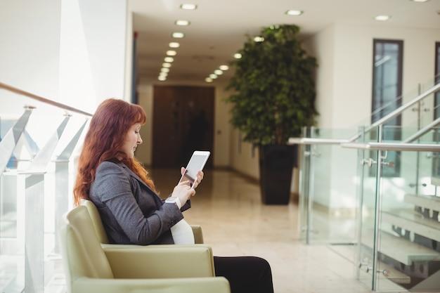 Zwangere zakenvrouw met behulp van digitale tablet in de buurt van gang