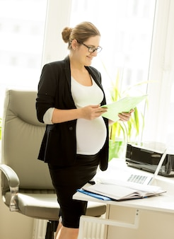 Zwangere zakenvrouw met dossier met documenten op kantoor