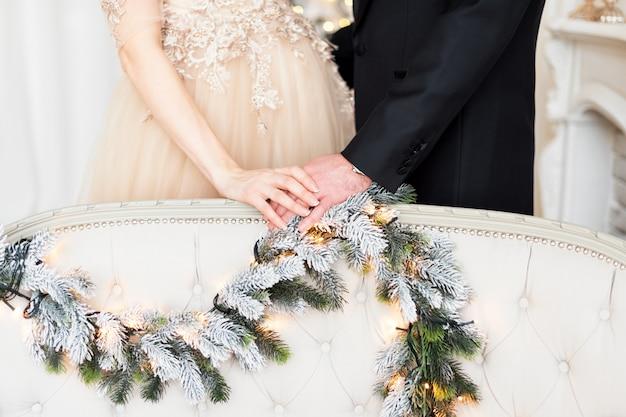 Zwangerschap, de wintervakantie en mensenconcept - sluit omhoog van de gelukkige handen van de paarholding bij kerstmis