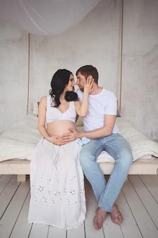 Zwangerschap en mensenconcept. gelukkig man knuffelen zijn mooie zwangere vrouw thuis. toekomstige ouders wachten ongeboren baby.