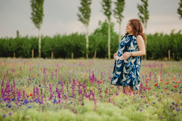 Zwangerschap en moederschap jonge vrouw verwacht een baby die blij is om plezier te hebben met haar toekomstige babyschoentjes die in de weide staan en vasthouden