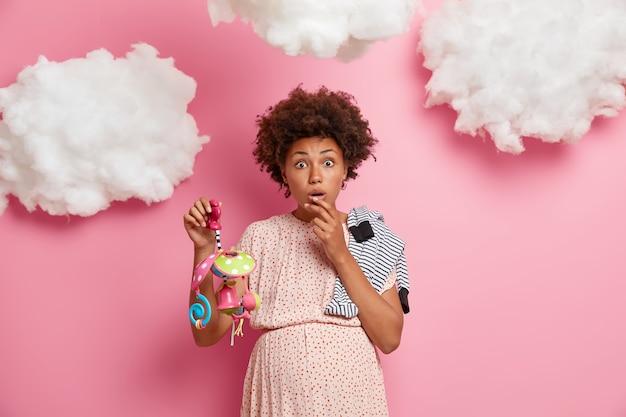 Zwangerschap en verwachting concept. onder de indruk toekomstige moeder geschokt om te ontdekken over enkele gezondheidsproblemen, angst voor moeilijkheden tijdens de bevalling, poseert met noodzakelijke items voor pasgeborenen