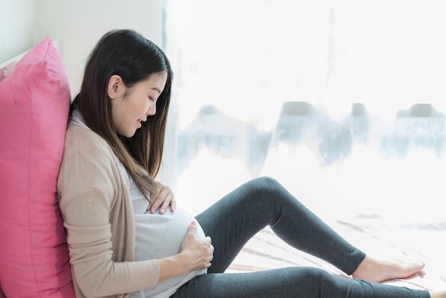 Zwangerschap is een geschenk. zwanger ontspannen in haar slaapkamer in bed.