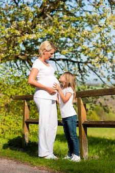 Zwangerschap - meisje wat betreft buik van zwangere moeder