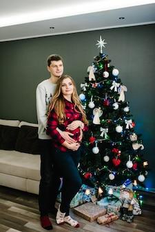 Zwangerschap, mensen en verwachting concept - gelukkige zwangere vrouw en man in de buurt van kerstboom interieur thuis. nacht kerstmis. genieten van gezinsvakanties. vrolijk kerstfeest en een gelukkig nieuwjaar.